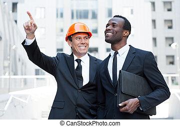 地位, 指すこと, hardhat, opportunities., 提示, 一緒に, 建築業者, 朗らかである, 間, アフリカ, ビジネスマン, 微笑, 離れて