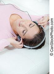 夫人, 躺在后面上, 听, 到, 頭戴收話器
