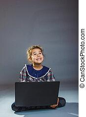 女の子, 子供, モデル, 遊び, ラップトップ, 驚かされる, 上に, a, グレーのバックグラウンド