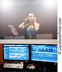 女の子, 身に着けていること, ヘッドホン, そして, 歌うこと, に, マイクロフォン, 中に, レコーディングスタジオ, コンピュータ装置, 中に, ∥, フレーム