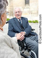 女性の保有物, 手, の, 年長 人, 中に, 車椅子, 話し