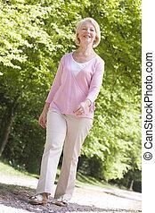 女性の歩くこと, 屋外で, 微笑