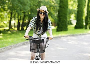 女性サイクリング, 公園, 若い, によって, 幸せ