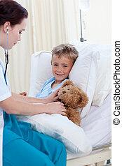 女性 醫生, 听, 到, a, 孩子, 胸膛, 以及, a, 玩具熊
