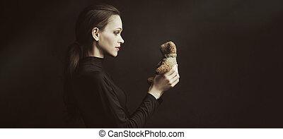 女, かなり, テディ, 上に, 手掛かり, 熊, おもちゃ, 黒い背景