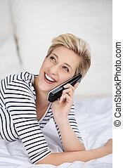 女, の上, ベッド, コードレス, 見る, 電話, 間, 使うこと