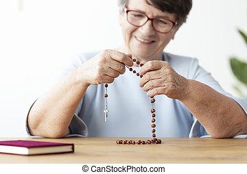 女, ロザリオ, フォーカス, 年配, 手, テーブル, 微笑, 祈ること, 宗教, bible.