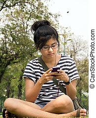 女, 座りなさい, 上に, 草, 発送, /, 受け取ること, a, テキスト メッセージ, /, 電子メール, 上に,...