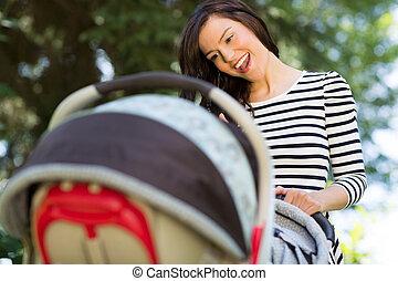 婦女看, 進, 嬰儿車, 在公園