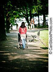 婦女走, 由于, 嬰儿車, 在公園