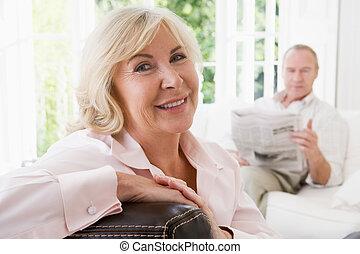 婦女, 在, 客廳, 微笑, 由于, 人, 在, 背景, 閱讀, 新聞