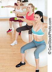 婦女, 訓練, 由于, dumbbells., 頂視圖, ......的, 三, 美麗, 年輕婦女, 在, 運動衣服, 藏品, dumbbells, 當時, 坐, 上, the, 健身 球