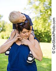婦女, 運載的兒子在肩膀, 在公園
