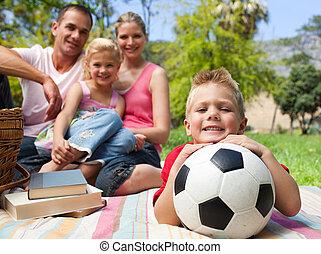 小男孩, 玩得高興, 由于, a, 足球, 由于, 他的, 家庭, 微笑, 在, the, 背景
