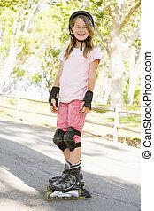 屋外で, 若い, スケート, インラインである, 微笑の女の子