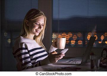 平机においての女性, 保有物, smartphone, 上に働く, ラップトップ, ∥において∥, night.