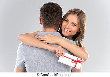 年輕夫婦, 擁抱, 由于, 包裹, present., 婦女, 擁抱, 人, 以及, 藏品, 禮物, 由于, 帶子