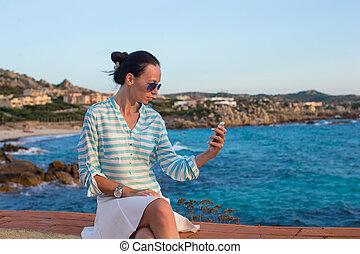 年輕婦女, 在電話上的談話, 在期間, 熱帶的海灘, 假期