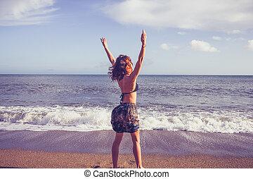 年輕婦女, 提高, 她, 武器, 在海灘