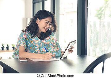 年輕, 亞洲人, 自由職業者, 婦女看, 到, 電腦, 片劑, 屏幕, 以及, 寫, 在懷特上, 紙, 在, 家庭辦公室