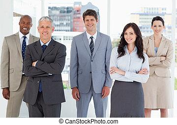 年輕, 微笑, 經理人, 站立, 在中間, ......的, the, 房間, 在中間, 他的, 同事