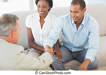 年轻夫妇, 握手, 带, 推销员, 在沙发上