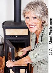 年長の 女性, パッティング, 木材を伐採する, woodburner