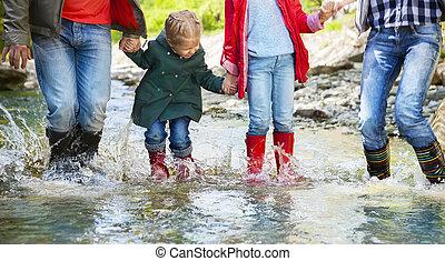 幸せな家族, 身に着けていること, 雨ブーツ, 跳躍, に, a, 山, 川