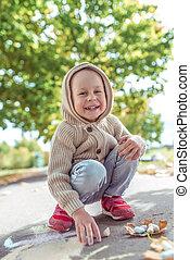 引く, セーター, 幸せ, クレヨン, 3-5, 偶然, 週末, 古い, 年, park., 笑い, ベージュ, わずかしか, ウエア, 歩きなさい, hood., asphalt., 有色人種, しゃがむ, 休む, 図画, smiles., 秋, 男の子, 暖かい