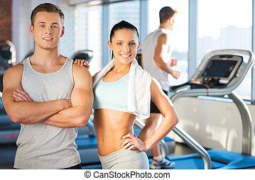 強有力, 以及, 充滿信心, 夫婦。, 美麗, 年輕夫婦, 結合, 到, 彼此, 以及, 微笑, 當時, 站立, 在, 體操, 由于, 踏車, 在, the, 背景
