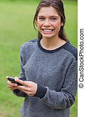 彼女, モビール, まっすぐに, 若い見ること, 電話, 間, カメラ, 成人, 使うこと, 微笑