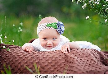 微笑的小女孩, 躺, 上, a, 毛毯, 在公園