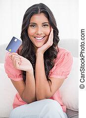 微笑, かわいい, ブルネット, ソファーの上に座る, 提示, クレジットカード
