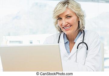 微笑, 女性 醫生, 使用便攜式計算机, 在, 醫學的辦公室