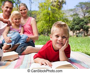 微笑, 小男孩, 閱讀, 躺在草上, 當時, 有一次野餐, 由于, 他的, 家庭, 在, a, 公園