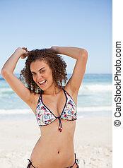 微笑, 年輕婦女, 提高, 她, 武器, 上面, 頭, 當時, 站在海灘上