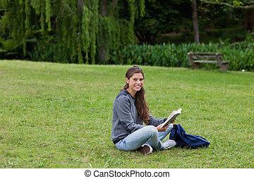 微笑, 若い 大人, 本を読む, 間, 脚を組んで 着席