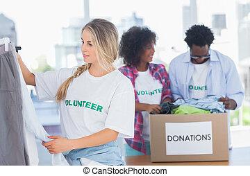 志愿者, 放, 衣服, 在, 衣服批評