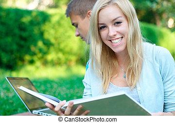 愉快, 女孩, 由于, a, 書, 由于, a, 學生, 上, the, 背景, 在, the, 公園