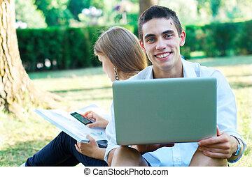 愉快, 年輕, 學生, 由于, 膝上型, 以及, a, 女孩, 在, the, 背景, 在, the, 公園
