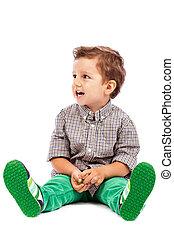愛らしい, 小さい 男の子, 床の上に座る, そして, ∥見る∥, 何か, に対して, 白い背景