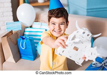 愛らしい, 男の子, 提示, 彼の, おもちゃの ロボット, そして, 微笑