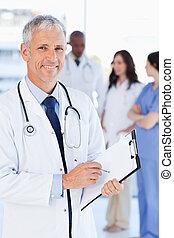 成熟醫生, 顯示, a, 重大的微笑, 當時, 指向, a, 詞, 上, 他的, 剪貼板