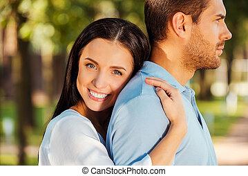 我, 愛, 他, 如此, much!, 美麗, 年輕婦女, 傾斜, 到, the, 背, ......的, 她, 男朋友, 以及, 微笑, 在照像机, 當時, 兩個都, 站立, 在戶外