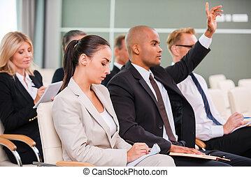 我, 有, a, question!, 生意人的組, 在, formalwear, 坐, 在, the, 椅子, 在, 會議大廳, 以及, 寫, 某事, 杜松子酒, 他們, 筆記, 墊, 當時, 漂亮, 非洲人, 提高, 他的, 手臂