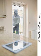 戸を通って, 見る, 台所, タブレットの pc, 強盗