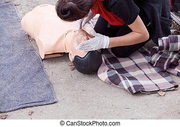 拿, a, pulse., 女性, 護理人員, 顯示, cardiopulmonary 复活, -, cpr, 上, 訓練, dummy.