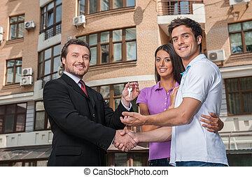 推销员, 给, 钥匙, 对于, 财产, owners., 握手交易, 带, 年轻夫妇, 在外面, 同时,, 调查照相机
