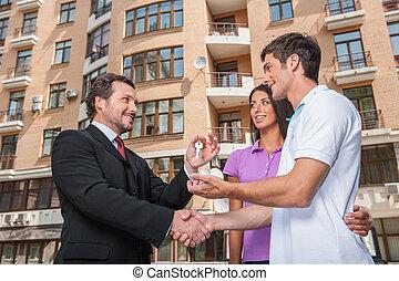 推销员, 给, 钥匙, 对于, 财产, owners., 握手交易, 带, 年轻夫妇, 在外面