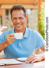 放松, 由于, 杯子, ......的, 新鮮, coffee., 快樂, 成熟的人, 喝咖啡, 以及, 微笑, 當時, 在桌旁坐, 在戶外, 由于, 房子, 在, the, 背景